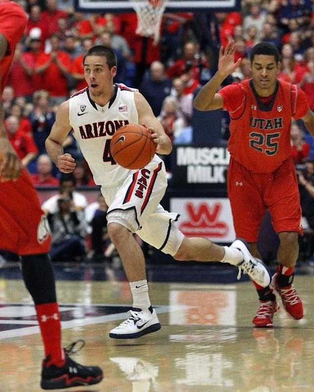 Arizona's T. J. McConnell (4) dribbles between Utah's Dakarai Tucker, left, and Kenneth Ogbe (25) in the first half of an NCAA college basketball game on Sunday, Jan. 26, 2014, in Tucson, Ariz. (AP Photo/John Miller)