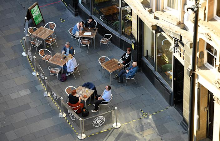 Customers sit outside bar in NewcastleAFP via Getty Images