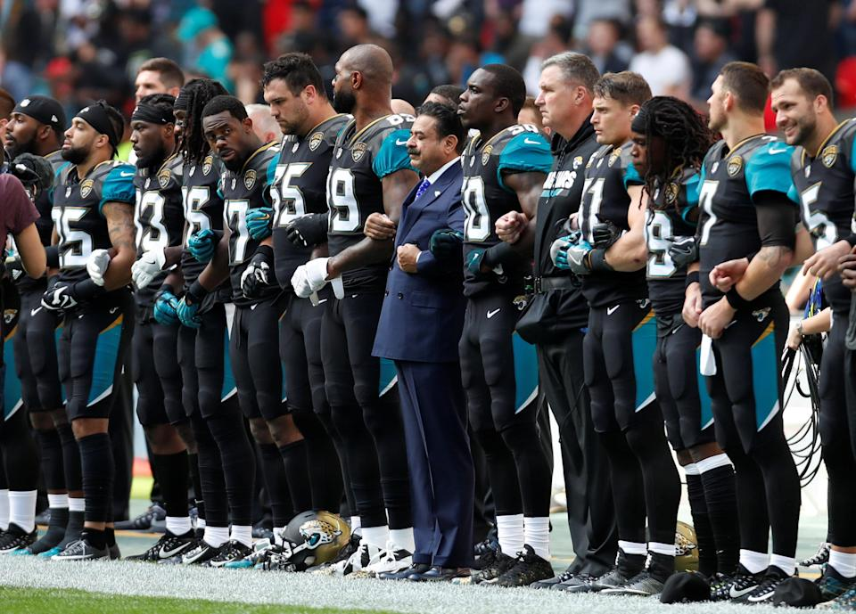 Jaguars owner Shad Khan links arms with players during the national anthem before the game. (Reuters)