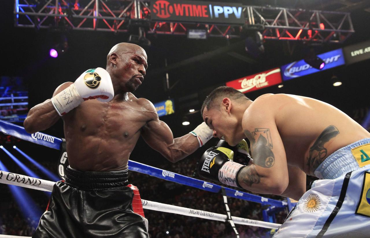 Floyd Mayweather Jr. (L) of the U.S. punches at Marcos Maidana of Argentina during their WBC/WBA welterweight unification fight at the MGM Grand Garden Arena in Las Vegas, Nevada, May 3, 2014. REUTERS/Steve Marcus (UNITED STATES - Tags: SPORT BOXING)