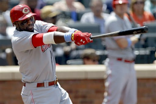 Cincinnati Reds' Brandon Phillips hits a fifth-inning, two-run single during their baseball game against the New York Mets at Citi Field in New York, Sunday, June 17, 2012. (AP Photo/Kathy Willens)