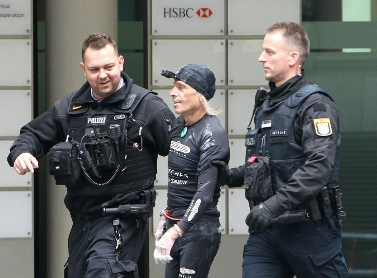 """French urban climber Alain Robert, popularly known as the """"French Spiderman"""", is led away by police after climbing the 154 metre high (500 foot) high Skyper building in Frankfurt"""