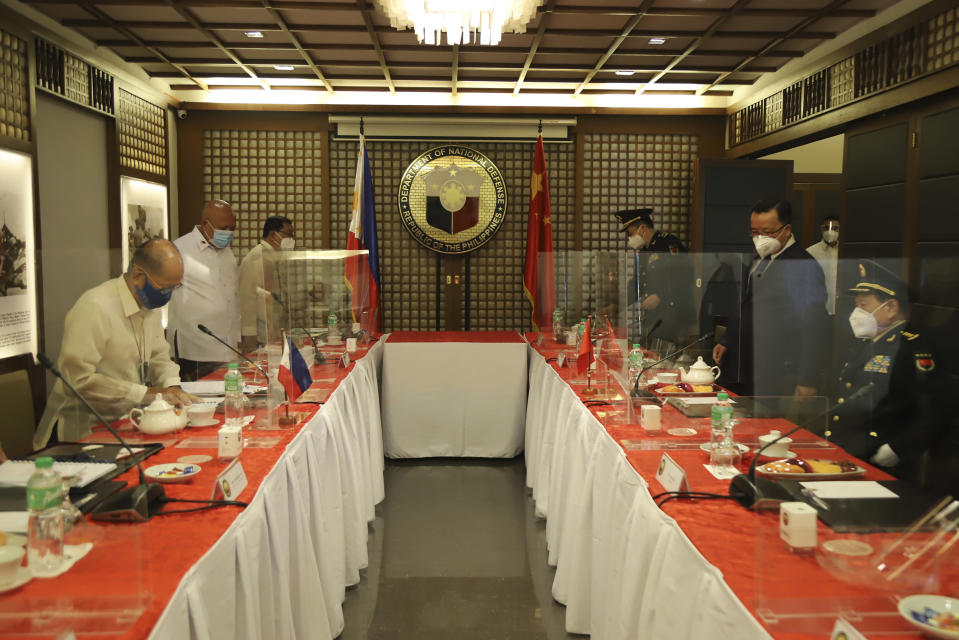 In this handout photo provided by the Department of National Defense Public Affairs Office (PAO), Philippine Defense Secretary Delfin N. Lorenzana, left, prepares to sit for a bilateral meeting with his Chinese counterpart General Wei Fenghe, right, at the Department of National Defense in Quezon city, Philippines, Friday Sept. 11, 2020. The two discussed ways in responding to the COVID-19 pandemic, revisited the 2004 Philippines-China Memorandum of Understanding (MOU) on Defense Cooperation and also issues on the South China Sea. (Department of National Defense PAO via AP)