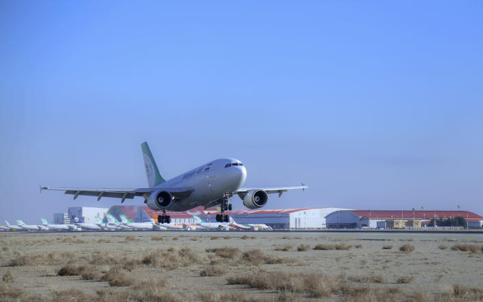 In this photo released by Imam Khomeini Airport City, an Iranian Mahan Air plane carrying Russian-made Sputnik V coronavirus vaccines lands at the Tehran's Imam Khomeini International Airport, Thursday, Feb. 4, 2021. Iran on Thursday received its first batch of foreign-made coronavirus vaccines as the country struggles to stem the worst outbreak of the pandemic in the Middle East. (Saeed Kaari/IKAC via AP)