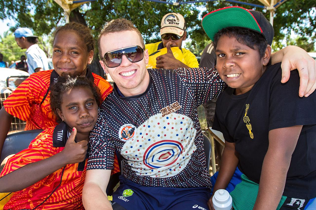 DARWIN, AUSTRALIA - AUGUST 10:  Peter Siddle of the Australian cricket team poses for photos with locals during a visit to Pirlangimpi of the Tiwi Islands on August 10, 2012 on the Tiwi Islands, Australia.  (Photo by Mark Nolan/Getty Images)