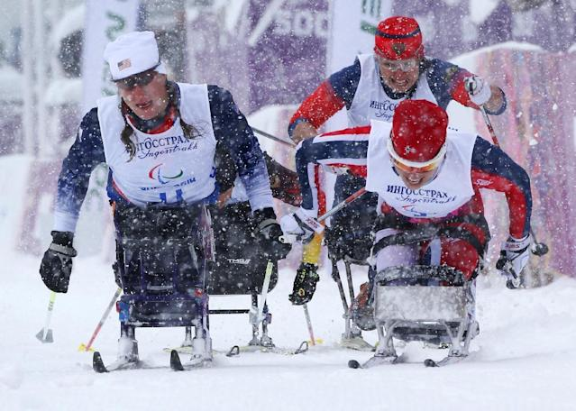 Mariann Marthinsen of Norway, right, 1st place, Tatyana Mcfadden of United States, left, 2nd place, and Marta Zaynullina of Russia, rear right, 3rd place, finish in final of the women's cross country 1km sprint, sitting event at the 2014 Winter Paralympic, Wednesday, March 12, 2014, in Krasnaya Polyana, Russia. (AP Photo/Dmitry Lovetsky)