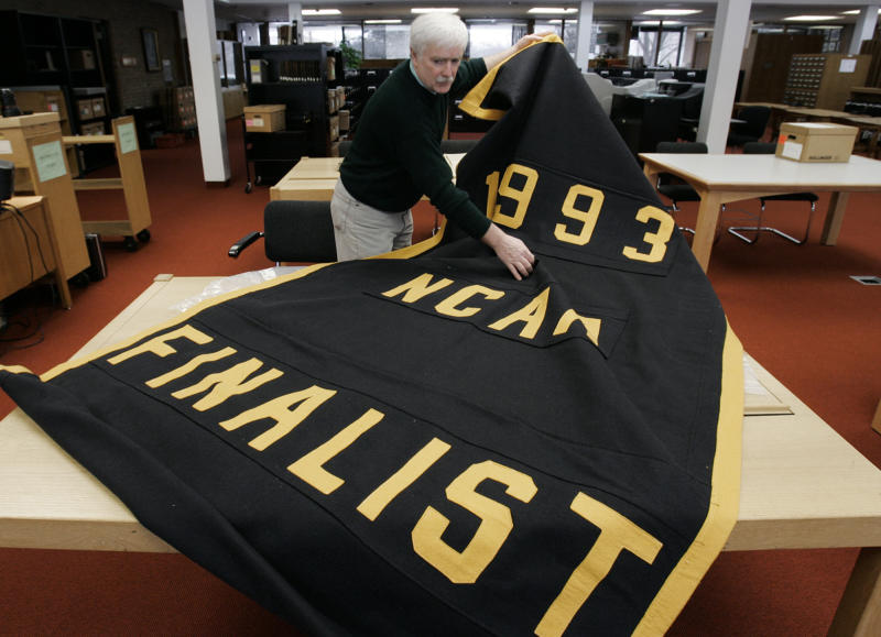FILE - In this Feb. 6, 2007,  file photo, Greg Kinney, archivist at the University of Michigan Bentley Historical Library unrolls the 1993 NCAA basketball tournament finalist banner being kept in storage in Ann Arbor, Mich. The banner was taken down from the university's Crisler Arena as part of self imposed sanctions following what the NCAA said was the largest financial scandal, and one of the worst of any kind, in the history of college athletics. Michigan's 10-year dissociation from Chris Webber, Maurice Taylor and Louis Bullock is over on May 8, 2013. The former Wolverines can formally reconnect with the school after one of the biggest scandals in NCAA history. Michigan athletic director Dave Brandon insisted the door is open. (AP Photo/Paul Sancya)