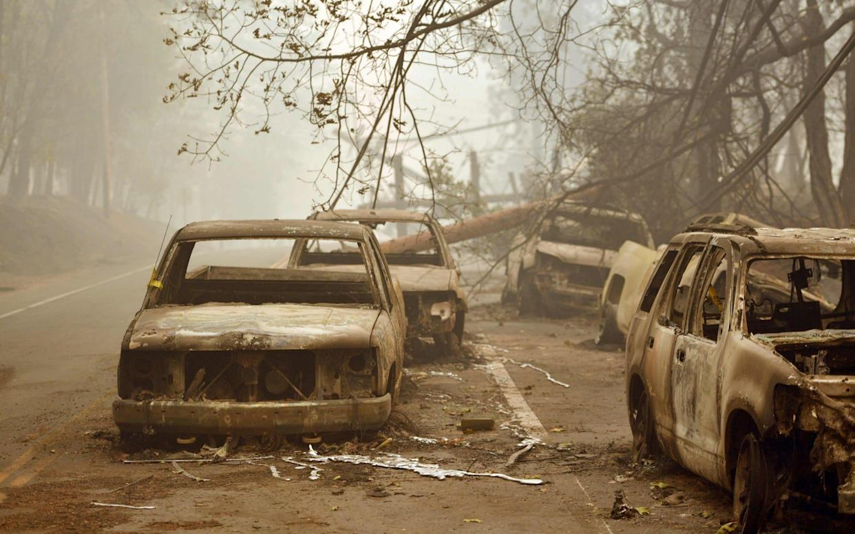 Burnt out vehicles are seen on the side of the road in Paradise, California - AFP