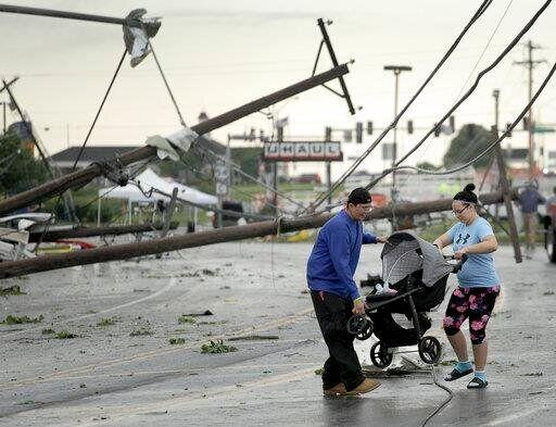 Jessica Rodgers and Ray Arellana carry a stroller carrying Rodgers' sister Sophia Rodgers over downed power lines.