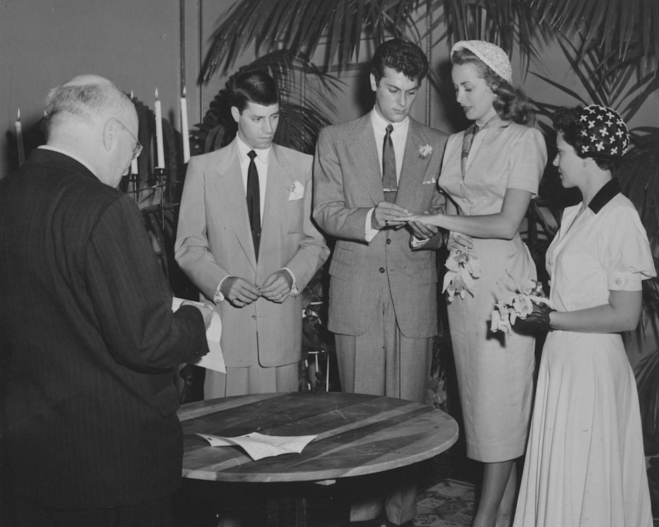 <p>Janet Leigh and Tony Curtis decided on an intimate affair at home in Greenwich, Connecticut. For the ceremony, Janet wore a mid-length, short-sleeved suit, a patterned scarf, and a white embroidered juliet cap. </p>