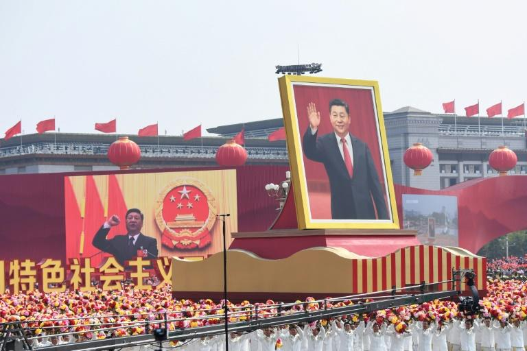 A float with a giant portrait of Chinese President Xi Jinping rolls through Tiananmen Square (AFP Photo/GREG BAKER)