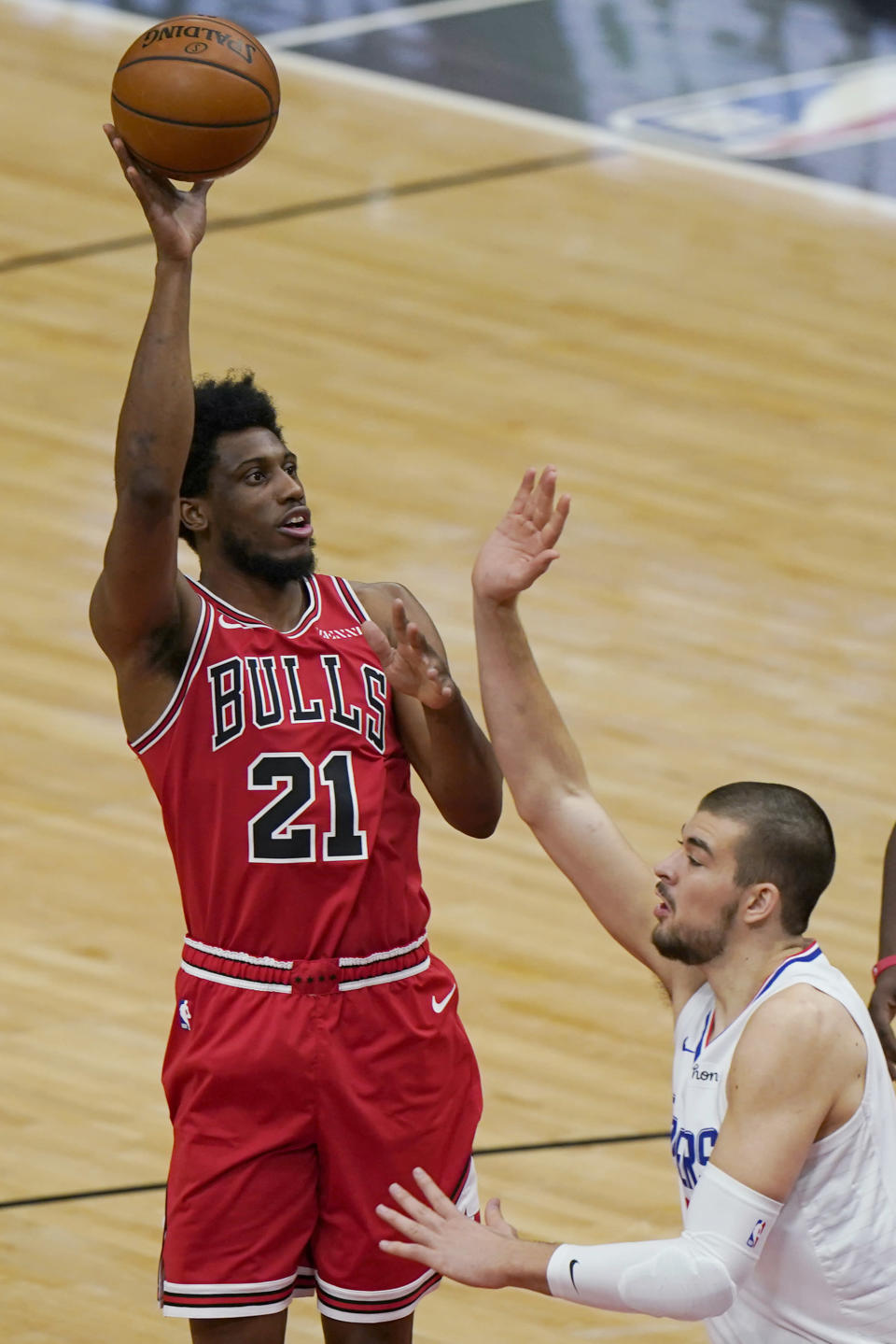 Chicago Bulls forward Thaddeus Young, left, shoots against Los Angeles Clippers center Ivica Zubac during the first half of an NBA basketball game in Chicago, Friday, Feb. 12, 2021. (AP Photo/Nam Y. Huh)