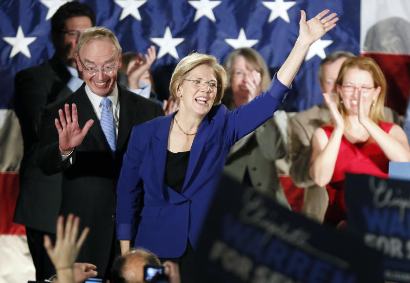 Democrat Elizabeth Warren, center, waves to the crowd with her husband Bruce Mann, left,  during an election night rally at the Fairmont Copley Plaza hotel in Boston after Warren defeated incumbent GOP Sen. Scott Brown in the Massachusetts Senate race, Tuesday, Nov. 6, 2012. (AP Photo/Michael Dwyer)