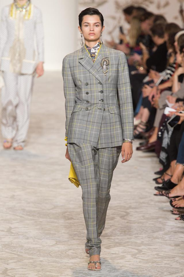 <p><i>Model wears a gray and yellow plaid suit with statement brooch and earrings from the SS18 Etro collection. (Photo: ImaxTree) </i></p>