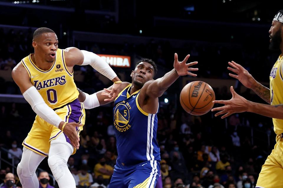 The Lakers' Russell Westbrook passes the ball to Anthony Davis while defended by Golden State Warriors' Kevon Looney.