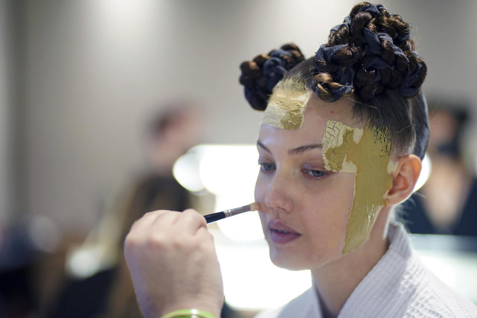 A model gets her makeup done backstage in preparation for the Thom Browne fashion show during New York Fashion Week at The Shed, on Saturday, Sept. 11, 2021, in New York. (Photo by Charles Sykes/Invision/AP)