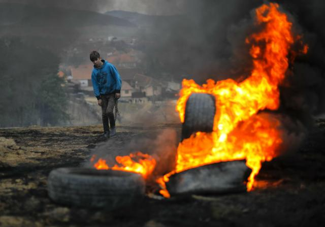 In this photo taken on Sunday, March 10, 2019, a boy walks holding a metal chain, during a ritual marking the upcoming Clean Monday, the beginning of the Great Lent, 40 days ahead of Orthodox Easter, on the hills surrounding the village of Poplaca, in central Romania's Transylvania region. Romanian villagers burn piles of used tires then spin them in the Transylvanian hills in a ritual they believe will ward off evil spirits as they begin a period of 40 days of abstention, when Orthodox Christians cut out meat, fish, eggs, and dairy. (AP Photo/Vadim Ghirda)