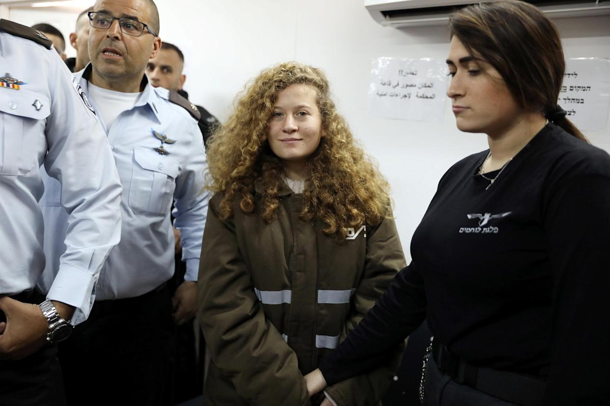 Palestinian teen Ahed Tamimi enters a military courtroom escorted by Israeli security personnel at Ofer Prison, near the West Bank city of Ramallah, Jan. 15, 2018. (Photo: Ammar Awad/Reuters)