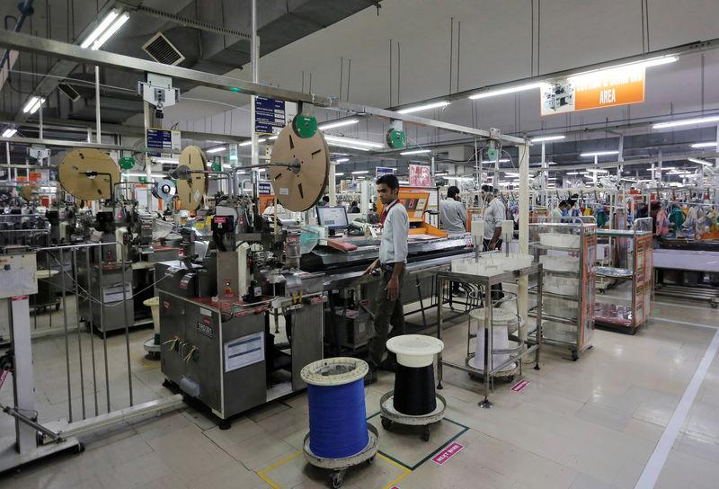 FILE PHOTO: Employees of Motherson Sumi Systems Ltd, work on a car wiring assembly line inside a factory in Noida