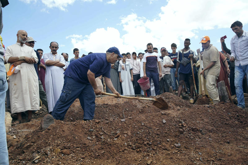 People dig graves during a funeral of residents who died in a flash flood in Tizert, near the southern region of Taroudant, Morocco. Thursday, Aug. 29, 2019. Morocco's official MAP news agency says that seven people watching a local soccer match in a southern village have died in a flash flood that swept across a football field on Wednesday evening. (AP Photo/Mohamed Amerkad)