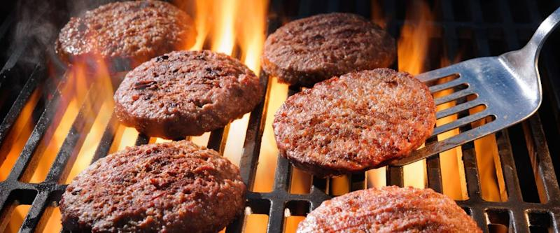 Juicy beef hamburger patties sizzling over hot flames on the barbecue