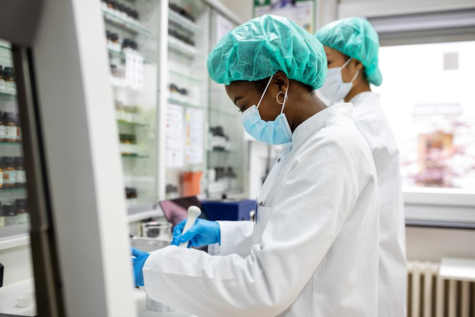 Two female scientists making medicine at a laboratory. Doctors working together at pharmacy lab wearing protective work wear.