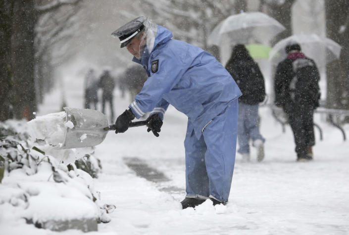 A security guard shoves snow from the street in Yokohama, Japan, Saturday, Feb. 8, 2014. The Japan Meteorological Agency issued the first heavy snowfall warning for central Tokyo in 13 years. Some 20-centimeter (7.9-inch) of snowfall is expected by Sunday morning in the metropolitan areas. (AP Photo/Eugene Hoshiko)