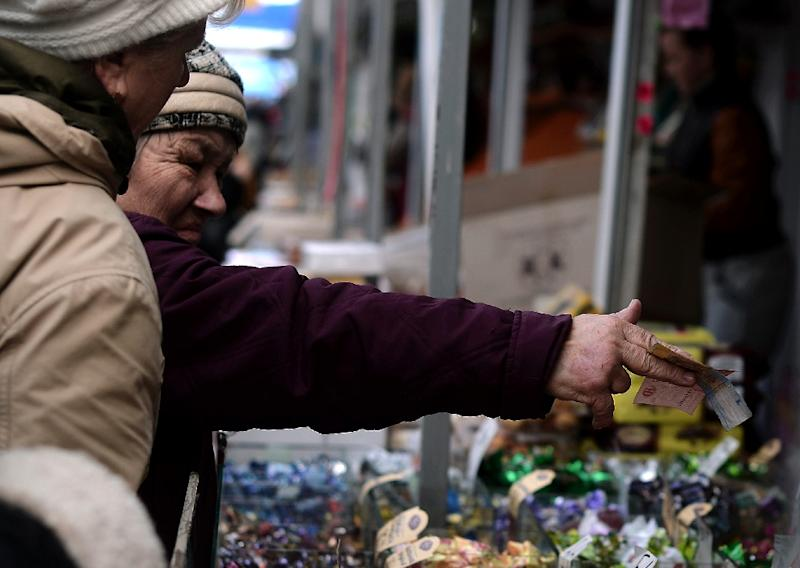 A woman pays with Ukranian Hryvnia as she shops in the main market in central Simferopol, in Crimea, on March 18, 2014