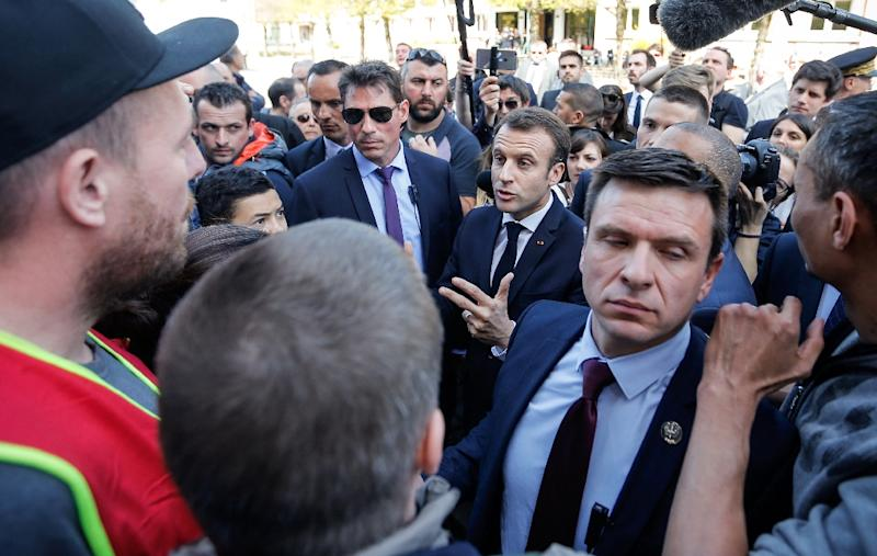"""Surrounded by bodyguards, French President Emmanuel Macron argues with demonstrators opposed to his reforms as he visited the """"coeur de ville"""" area of Saint-Die-des-Vosges, eastern France, on April 18, 2018 as part of a three-day-visit to the region (AFP Photo/Vincent KESSLER)"""