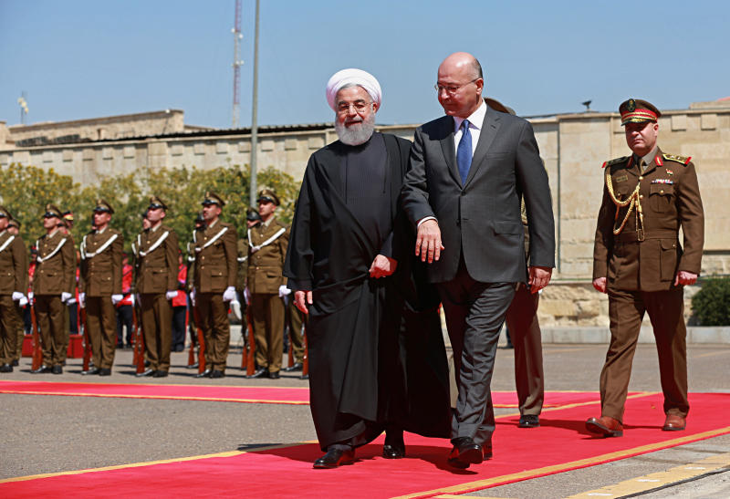 Iraqi President Barham Salih, center, walks with visiting Iranian President Hassan Rouhani, before their meeting at Salam Palace in Baghdad, Iraq, Monday, March 11, 2019. Rouhani is visiting Iraq, seeking to boost ties between the two neighboring states and possibly secure Iraq's help in bypassing U.S. sanctions the Trump administration re-imposed last year. (AP Photo/Khalid Mohammed)