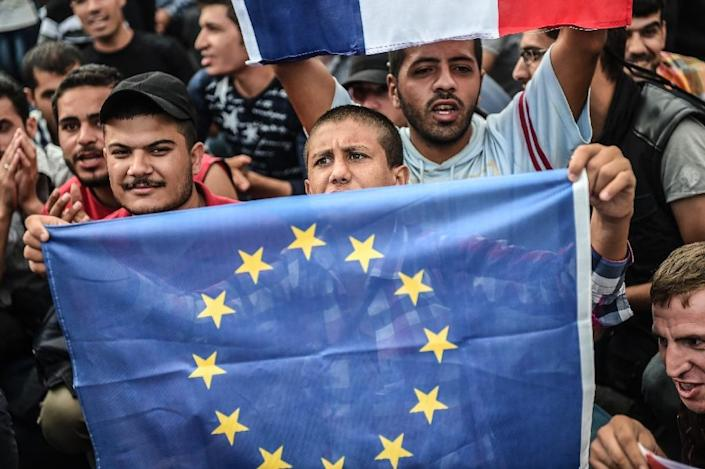 A migrant holds a European Union flag during a demonstration at Istanbul's Esenler bus terminal on September 19, 2015 (AFP Photo/Ozan Kose)