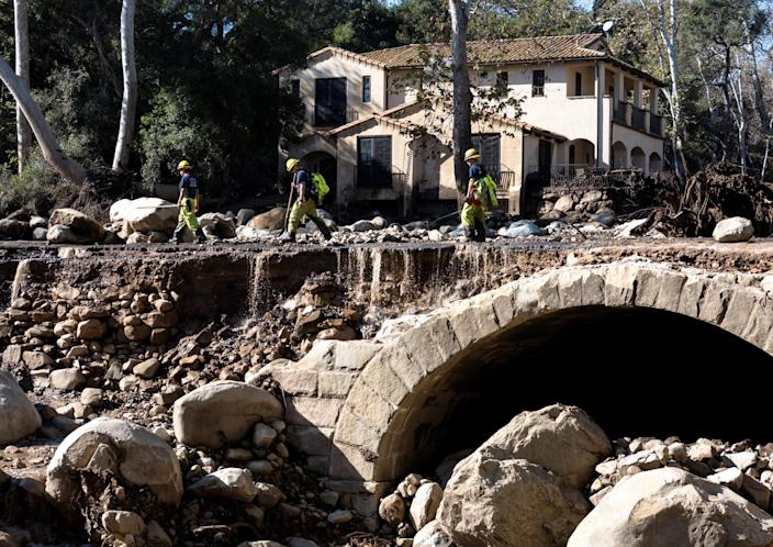 <p>Montecito firefighters walk on a road damaged by mudslides in Montecito, Calif., Jan. 10, 2018. (Photo: Kenneth Song/Santa Barbara News-Press via Reuters) </p>