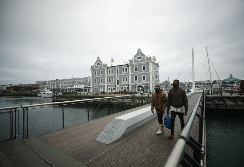 Masked visitors cross a bridge in the popular Waterfront district in Cape Town