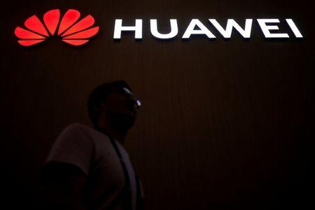 FILE PHOTO: A man walks past a sign board of Huawei at CES (Consumer Electronics Show) Asia 2018 in Shanghai