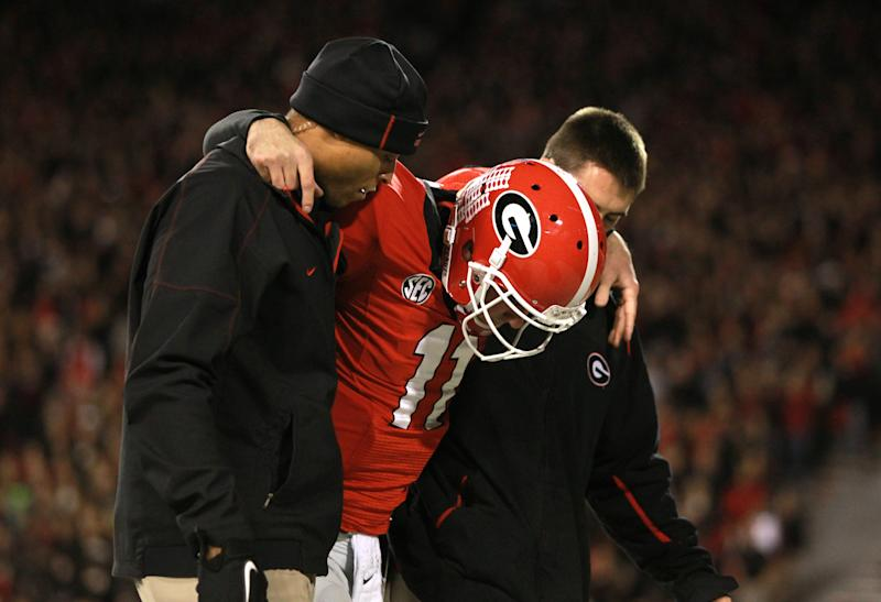 Georgia Bulldogs quarterback Aaron Murray (11) is helped off of the field by trainers after he was injured on a play in the first half of their game against the Kentucky Wildcats at Sanford Stadium Saturday night in Athens, Ga., Nov. 23, 2013. Murray, a senior, threw four touchdown passes and one interception in the first half of his final home game of the season. (AP Photo/Atlanta Journal-Constitution, Jason Getz)