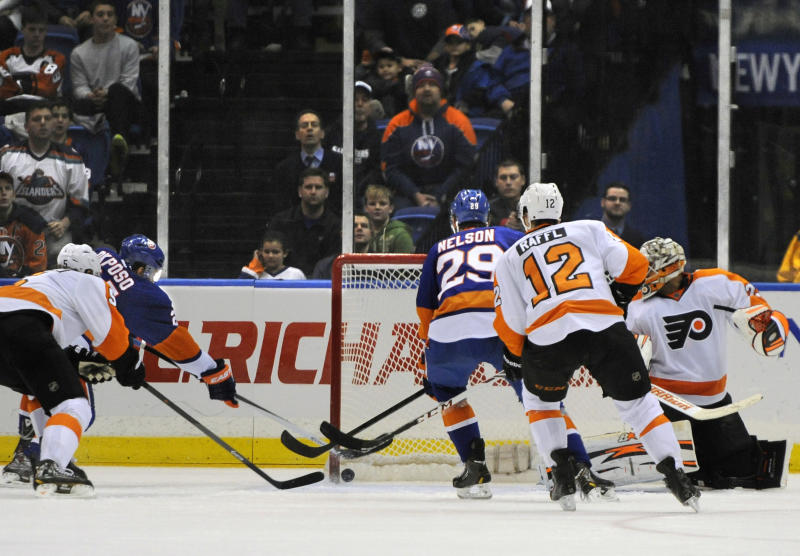 New York Islanders' Kyle Okposo (21) drives the puck past Philadelphia Flyers goalie Ray Emery (29) and Braydon Coburn (5) to tie the score 3-3 as Islanders' Brock Nelson (29) and Flyers' Michael Raffl (12) watch from behind in the third period of an NHL hockey game on Monday, Jan. 20, 2014, in Uniondale, N.Y. The Islanders won 4-3 in a shootout. (AP Photo/Kathy Kmonicek)