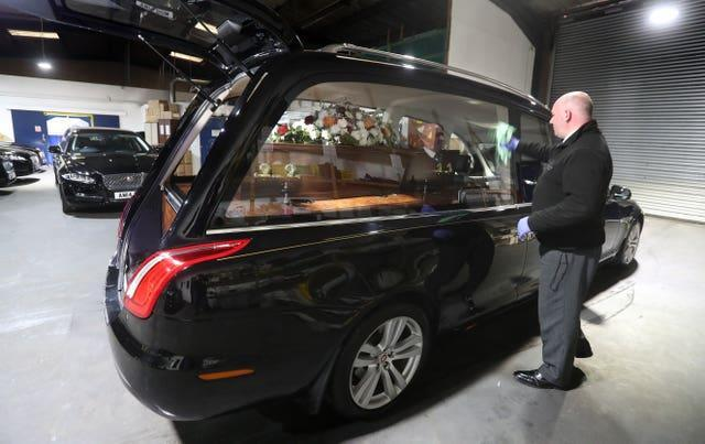 Christopher Bradley from Anderson Maguire Funeral Directors polishes a hearse at their offices in Glasgow (Andrew Milligan/PA)