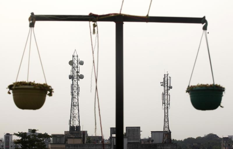 Telecommunication towers are pictured through hanging flower pots at a residential building in Kolkata