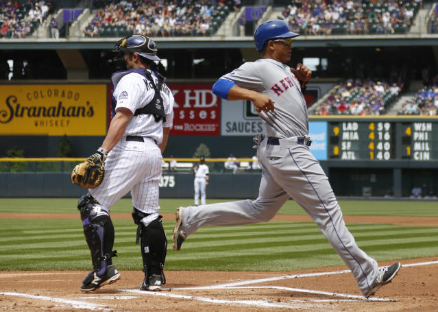 New York Mets' Juan Legares, front, scores on a single by Curtis Granderson as Colorado Rockies catcher Michael McKenry waits for the throw from the outfield in the first inning of a baseball game in Denver on Sunday, May 4, 2014. (AP Photo/David Zalubowski)