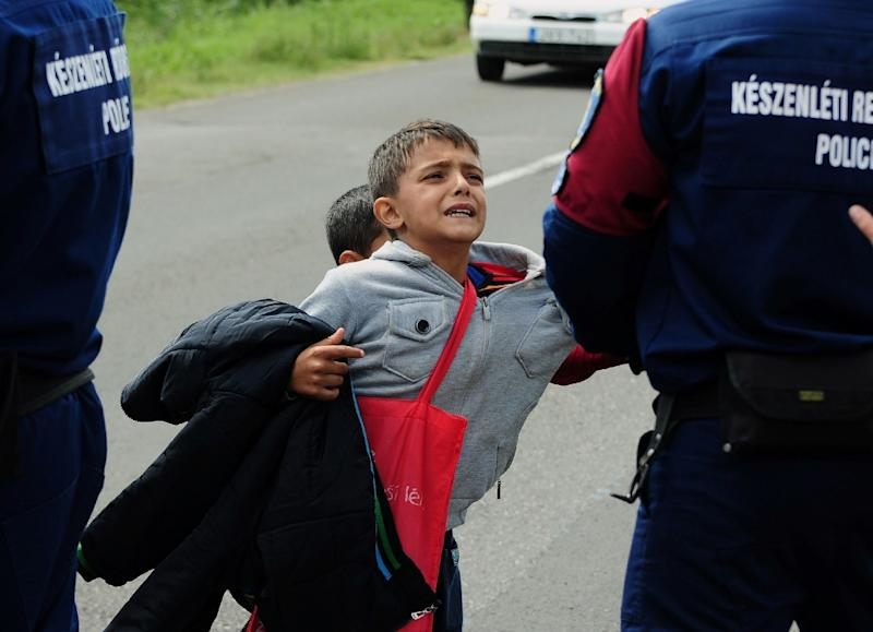 Police officers hold a migrant child after a crowd of refugees broke out of at collection point near Roszke village at the Hungarian-Serbian border on September 9, 2015 (AFP Photo/Csaba Sefesvari)