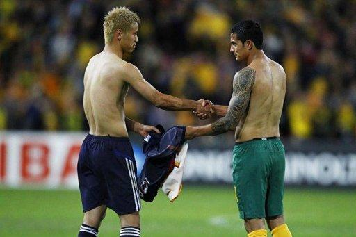 Japan's Keisuke Honda (L) exchanges jersey's with Australian player Tim Cahill