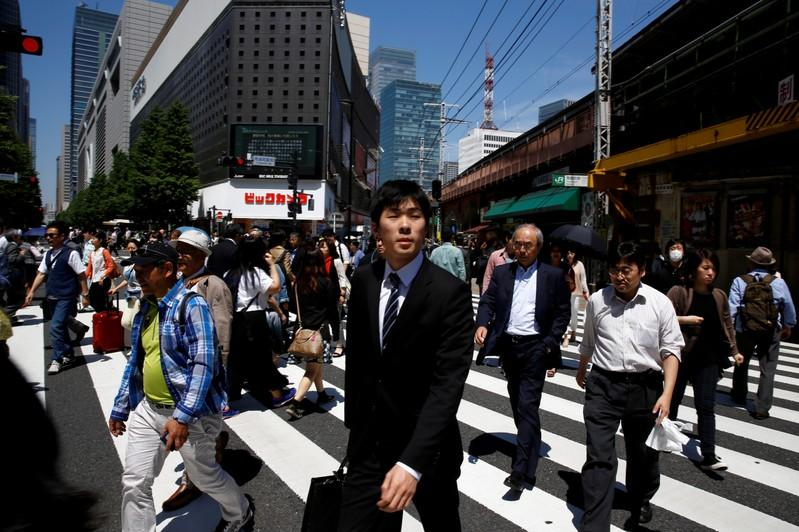 FILE PHOTO: People cross a junction in front of an electronics retailer in a business district in Tokyo