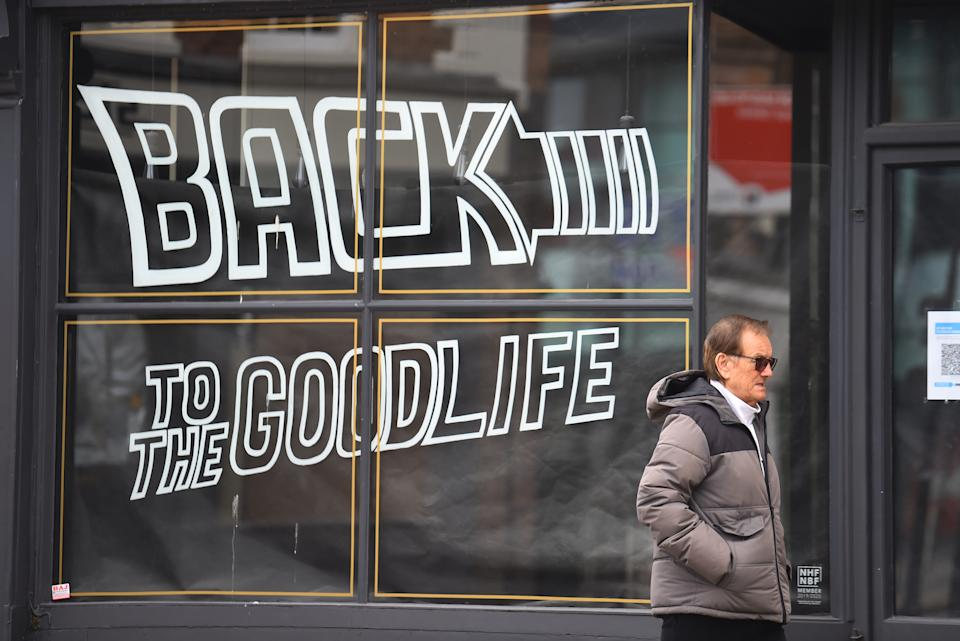 A man walks past a shop sign saying 'back to the goodlife' in Worcester town centre, England. Photo: Nathan Stirk/Getty Images