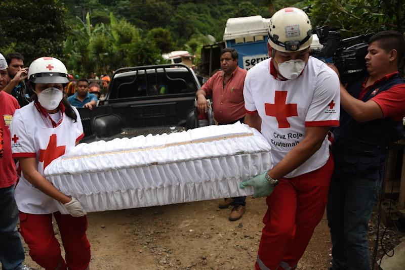Members of the Red Cross carry a small coffin with the remains of a victim pulled out of the debris in the village of El Cambray II, some 15 km east of Guatemala City, on October 3, 2015 (AFP Photo/Johan Ordonez)