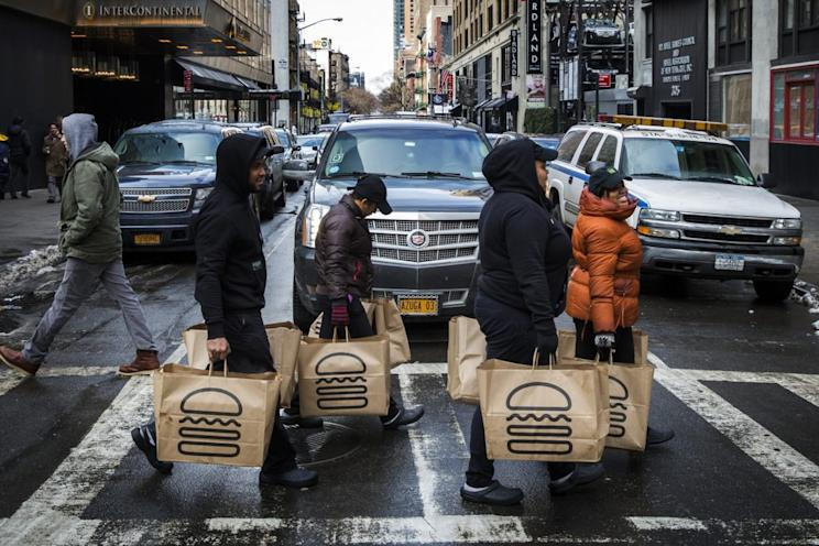 Employees carry delivery bags full of food out of a Shake Shack store in New York January 30, 2015. REUTERS/Lucas Jackson