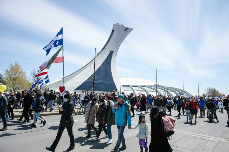 Demonstrators in Montreal march past the Olympic Stadium in a protest against Covid-19 restrictions on May 1, 2021