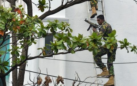 Sri Lankan Special Task Force (STF) personnel climb a ladder outside a house during a raid  - Credit:  ISHARA S. KODIKARA/AFP