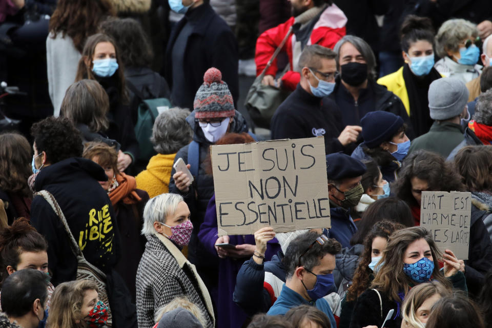 Workers from the cultural sector gather during a protest, in Paris, Tuesday, Dec.15, 2020. Representatives of the performing arts sector protested against the ongoing closure of theaters and cinemas in the country as France on Tuesday is lifting a lockdown imposed on 30 October, but strict measures are still in place as infections are still high. The board reads: I'm non essential. (AP Photo/Christophe Ena)