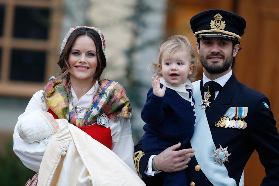 Prince Gabriel of Sweden held by Princess Sofia of Sweden and Prince Carl Philip holding Prince Alexander