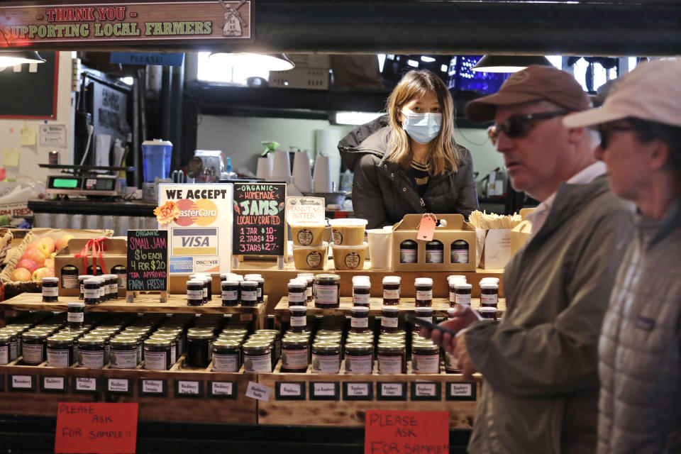 Vendor Belle Naing watches people walk past her jam and produce stand at the Pike Place Market, Friday, March 20, 2020, in Seattle. Many shops in the landmark market, including fish, meat, bakeries and produce grocers, continue to remain open, though business has dropped considerably in recent weeks. Restaurants, except for take-out orders, are closed, workers who can are working from home and people are being asked to maintain physical distance from others to help stop the spread of COVID-19. Washington state health officials reported eight new coronavirus deaths on Friday, bringing the total to 83. Seven of those deaths were in King County, the epicenter of the outbreak in the state. (AP Photo/Elaine Thompson)